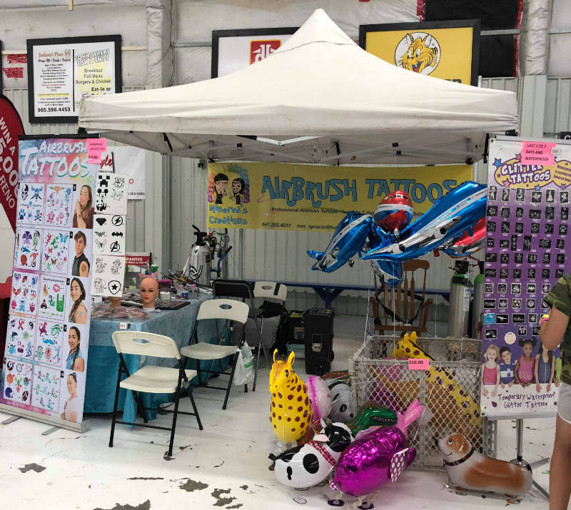 Minerva's Creations booth offering face painting and balloon twisting for events in Aurora, Newmarket, Innisfil, Mount Albert, Beeton, Barrie, Keswick