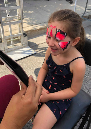 event face painting in Northyork, Toronto and Mississauga - girl delighted with her face painting