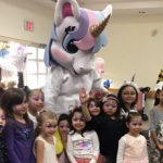 children posing for a picture with unicorn mascot
